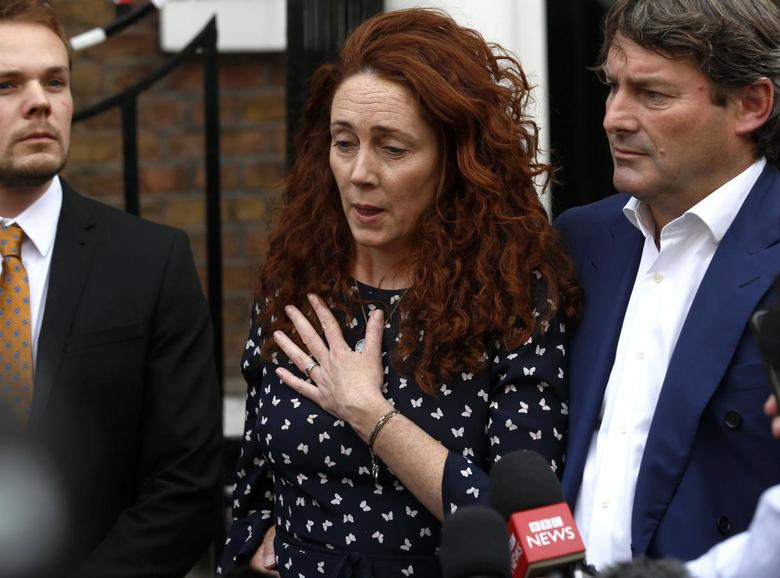 Former News International chief executive Rebekah Brooks places her hand on her heart as she makes a statement to the media alongside her husband Charlie in London June 26, 2014.  REUTERS/Luke MacGregor