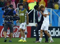 O técnico da seleção da Coreia do Sul, Hong Myung-bo, consola o jogador sul-coreano Son Heung-min após derrota para a Bélgica na partida pelo Grupo H da Copa do Mundo, na Arena Corinthians, em São Paulo. 26/06/2014.  REUTERS/Eddie Keogh