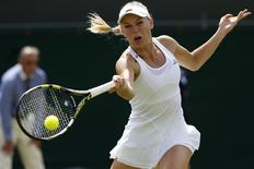 Caroline Wozniacki of Denmark hits a return to Ana Konjuh of Croatia during their women's singles tennis match at the Wimbledon Tennis Championships, in London June 27, 2014. REUTERS/Suzanne Plunkett