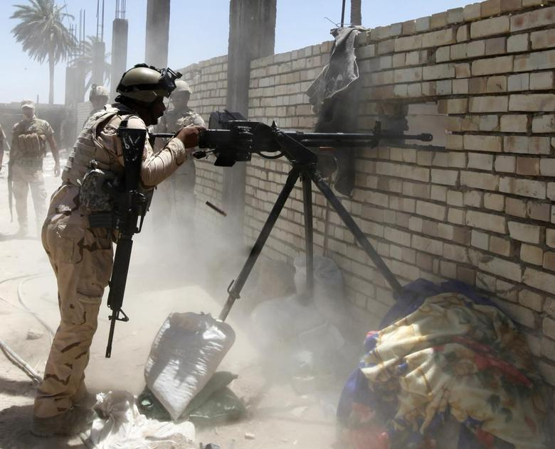 A member of the Iraqi security forces opens fire during clashes with fighters from Sunni militant group Islamic State of Iraq and the Levant (ISIL) in Ibrahim bin Ali village, west of Baghdad, June 24, 2014. REUTERS/Ahmed Saad