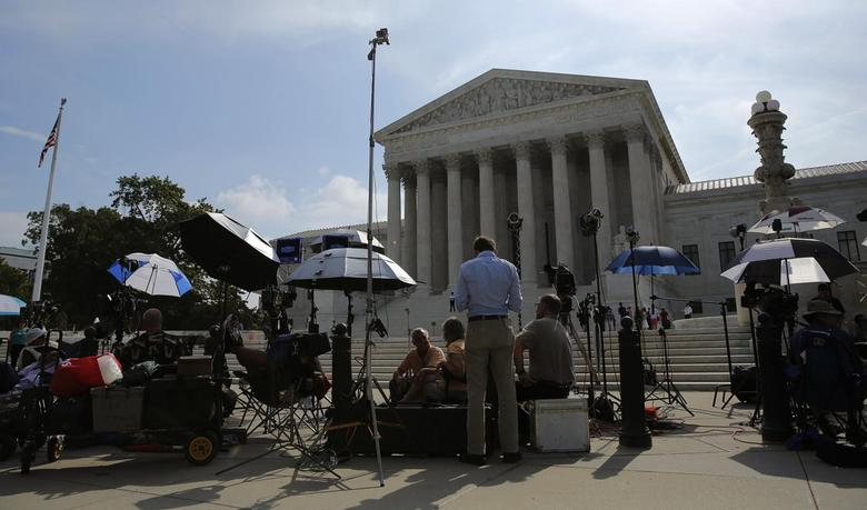Numerous news crews await outside the Supreme Court in Washington June 25, 2014 file photo. The Court is expected to rule on several key cases in this term, most notably the Hobby Lobby contraception case that asks whether owners of companies with strongly held religious views can seek an exemption from the birth control provisions of the Affordable Care Act, also known as Obamacare.    REUTERS/Gary Cameron