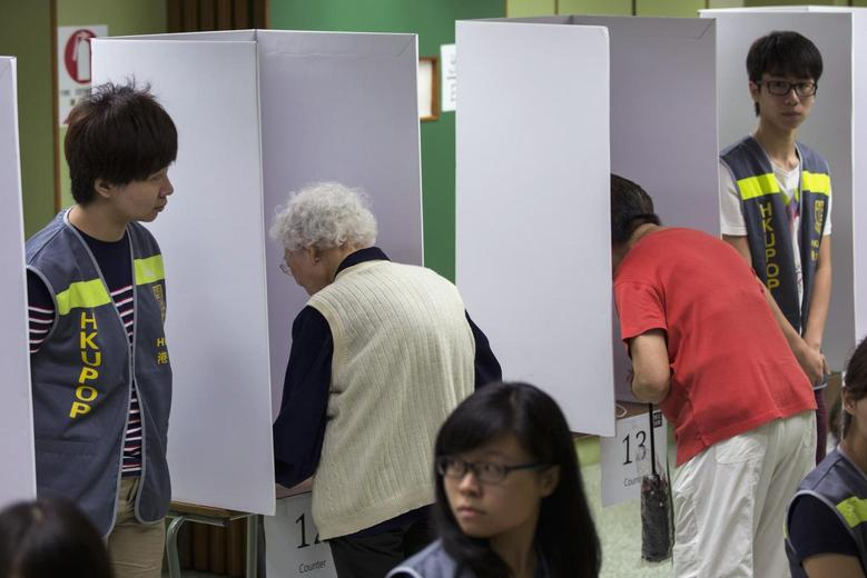 People vote at a polling station during a civil referendum held by Occupy Central in Hong Kong June 29, 2014.    REUTERS/Tyrone Siu
