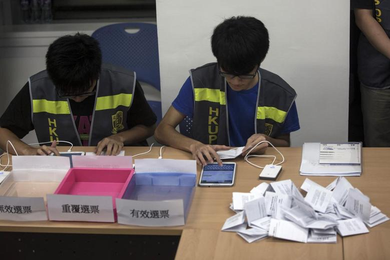 Electoral assistants count ballots at a polling station after the last day of civil referendum held by the Occupy Central organisers in Hong Kong June 29, 2014. REUTERS/Tyrone Siu