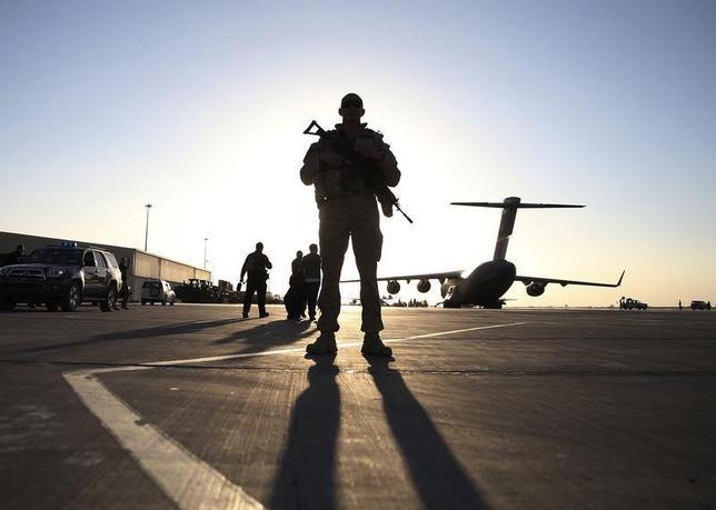A soldier stands guard near a C-17 Globemaster III aircraft sitting on the tarmac at Kandahar Air Base December 8, 2013.  REUTERS/Mark Wilson/Pool