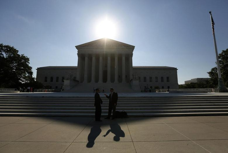 Two men talk as the sun rises over the Supreme Court in Washington June 23, 2014. REUTERS/Kevin Lamarque