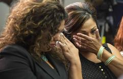 Rosie Cortinas (L) and Monica Coronado, who are family members of General Motors crash victims, wipe their eyes as Kenneth Feinberg, a victims compensation lawyer hired by General Motors, speaks in Washington June 30, 2014. Feinberg was speaking at a news conference to announce the eligibility criteria for a program to compensate victims of a faulty ignition switch that prompted the recall of 2.6 million vehicles. REUTERS/Joshua Roberts