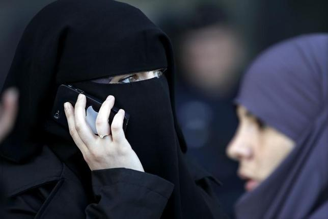 A women, wearing a niqab despite a nationwide ban on the Islamic face veil, gives a phone call outside the courts in Meaux, east of Paris, September 22, 2011.  REUTERS/Charles Platiau