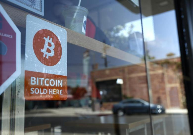 A bitcoin sticker is seen in the window of Locali Conscious Convenience store, where one of Southern California's first two bitcoin-to-cash ATMs began operating today, in Venice, Los Angeles, California, June 21, 2014. REUTERS/Lucy Nicholson
