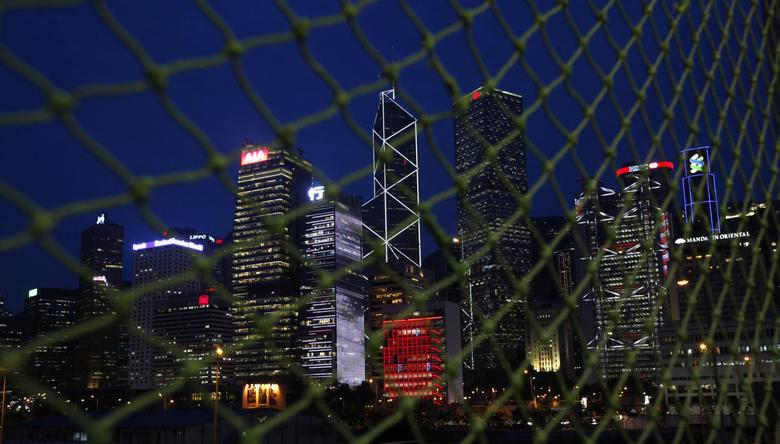 Skyscrapers at Hong Kong's central business district (L-R) AIA Central, CCB Tower, Bank of China Tower, City Hall (in red), Cheung Kong Centre, HSBC headquarters and Standard Chartered Bank are seen behind a net near a construction site moments after sunset June 10, 2014.   REUTERS/Bobby Yip