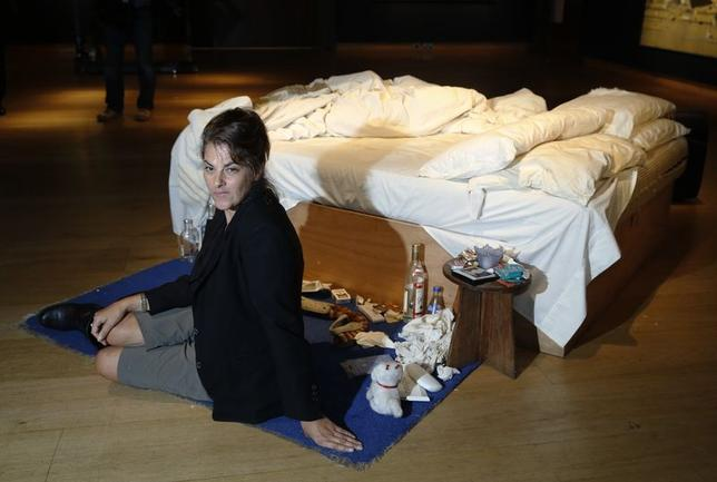 Artist Tracey Emin poses with her conceptual artwork ''My Bed'' at Christie's auction house in London June 27, 2014. REUTERS/Luke MacGregor