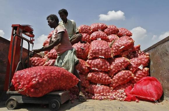 A man weighs a sack of onions before unloading it from a supply truck at a wholesale market in Chennai February 4, 2013. REUTERS/Babu/Files