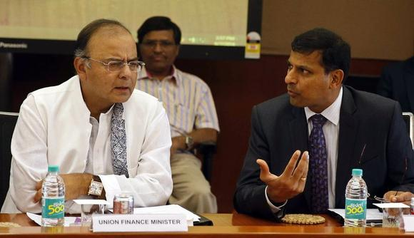 India's new Finance Minister and Defence Minister Arun Jaitley (L) listens to Reserve Bank of India (RBI) Governor Raghuram Rajan during a financial stability development council meeting in Mumbai June 7, 2014. REUTERS/Stringer
