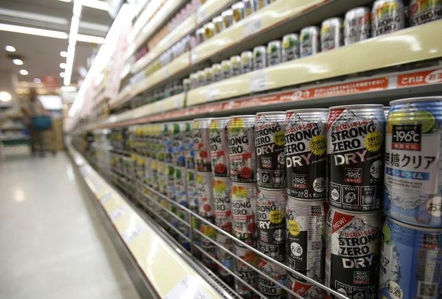 Cans of Suntory Holdings' ''Strong Zero Dry'' vodka tonic are displayed with other ready-to-drink cans of alcohol as a man shops at a supermarket in Tokyo June 29, 2014. REUTERS/Yuya Shino