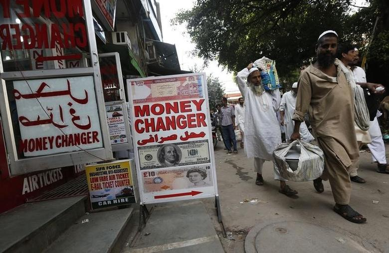 Men walk past a currency exchange shop in New Delhi August 21, 2013. REUTERS/Adnan Abidi/Files