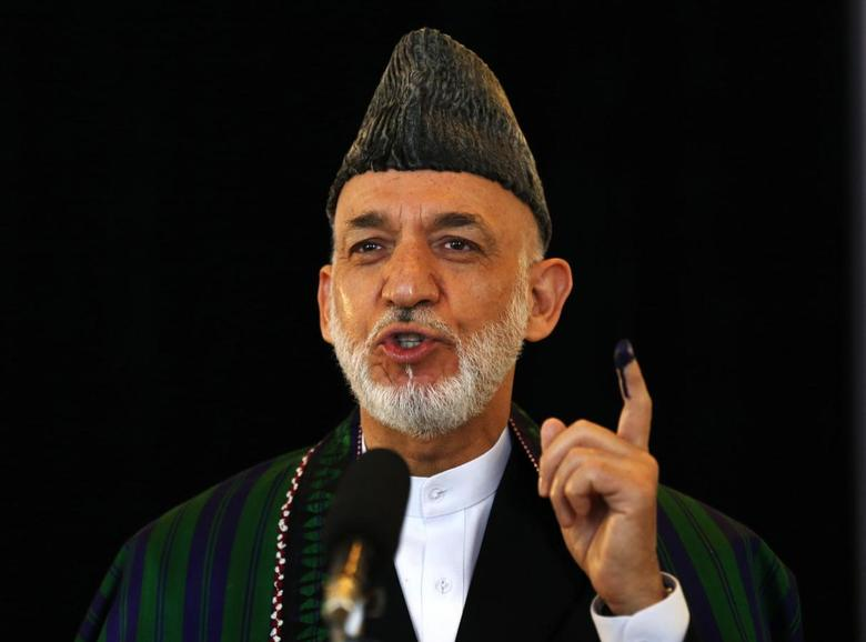 Afghan President Hamid Karzai holds up his ink-stained finger after voting in the presidential election in Kabul June 14, 2014. REUTERS/Mohammad Ismail