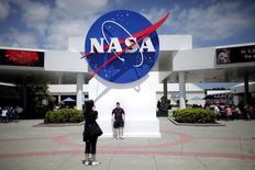 En la imagen, unos turistas toman fotos de un cartel de la NASA en Cabo Cañaveral, Florida, 14 de abril de 2010.  La compañía estadounidense Boeing anunció la firma de un contrato por 2.800 millones de dólares con la agencia espacial NASA para desarrollar la etapa central de su Sistema de Lanzamiento Espacial (SLS, por sus siglas en inglés). REUTERS/Carlos Barria