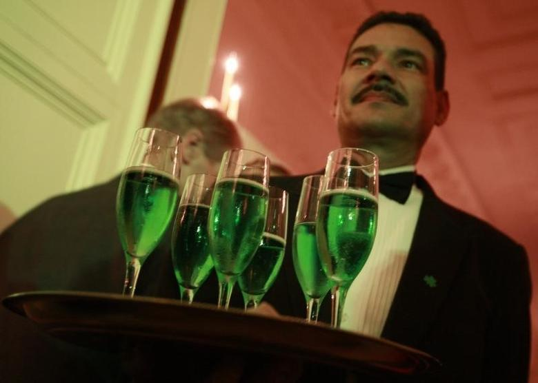 A waiter serves green champagne to guests during a St. Patrick's Day reception hosted by President Barack Obama in the East Room of the White House in Washington, March 17, 2009.     REUTERS/Jason Reed