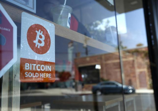 A bitcoin sticker is seen in the window of Locali Conscious Convenience store, in Venice, Los Angeles, California, June 21, 2014. REUTERS/Lucy Nicholson