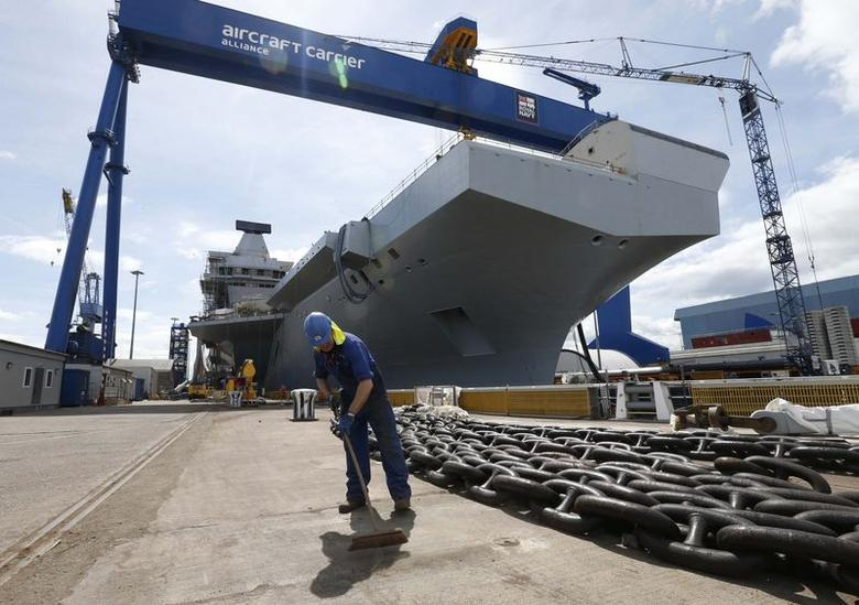 A worker sweeps in front of HMS Queen Elizabeth, the first of two aircraft carriers being built by British defence firm BAE Systems, at the Rosyth Dockyard in Fife, Scotland June 17, 2014.  REUTERS/Russell Cheyne