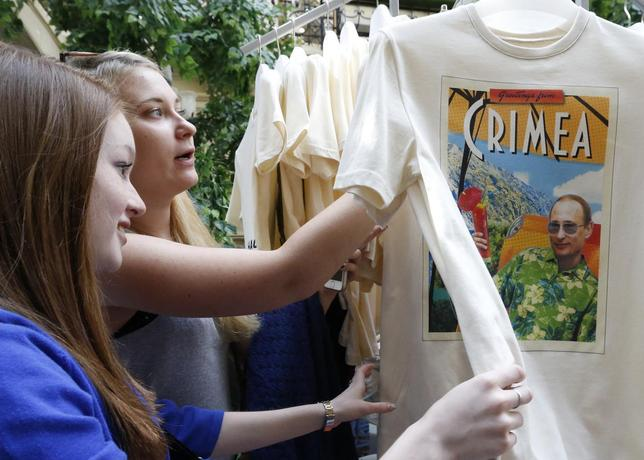 Women inspect T-shirts, displaying images of Russia's President Vladimir Putin, which are on sale at GUM department store in central Moscow, June 11, 2014.  REUTERS/Sergei Karpukhin