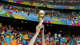 A Netherlands fan holds up a replica trophy during the match. REUTERS/Paul Hanna