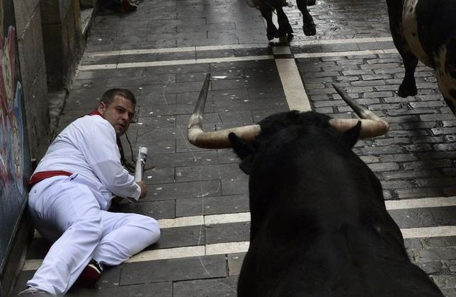 A runner falls in front of a Torrestrella fighting bull at the Estafeta corner during the first running of the bulls at the San Fermin festival in Pamplona July 7, 2014.  REUTERS/Vincent West