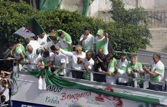 Técnico da seleção da Argélia, Vahid Halilhodzic, ergue uma bandeira da Argélia durante recepção aos jogadores no centro de Argel. 2/07/2014. REUTERS/Louafi Larbi