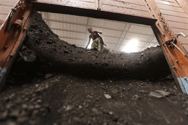A worker unloads coal from a truck inside a coal yard at Saroda village in Gujarat July 5, 2014.  REUTERS/Amit Dave