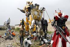 """Рабочие собирают копии роботов-трансформеров на окраине Шанхая 18 июня 2014 года. Новая часть экшена про роботов-пришельцев """"Трансформеры: Эпоха истребления"""" собрала $36,4 миллиона за второй уикенд в США и Канаде, не пустив на вершину проката новичков - """"Тэмми"""" и """"Избави нас от лукавого"""". REUTERS/Aly Song"""