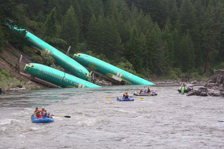 Three Boeing 737 fuselages lie on an embankment on the Clark Fork River after a BNSF Railway Co train derailed Thursday near Rivulet, Montana in this picture taken July 4, 2014. REUTERS/Kyle Massick