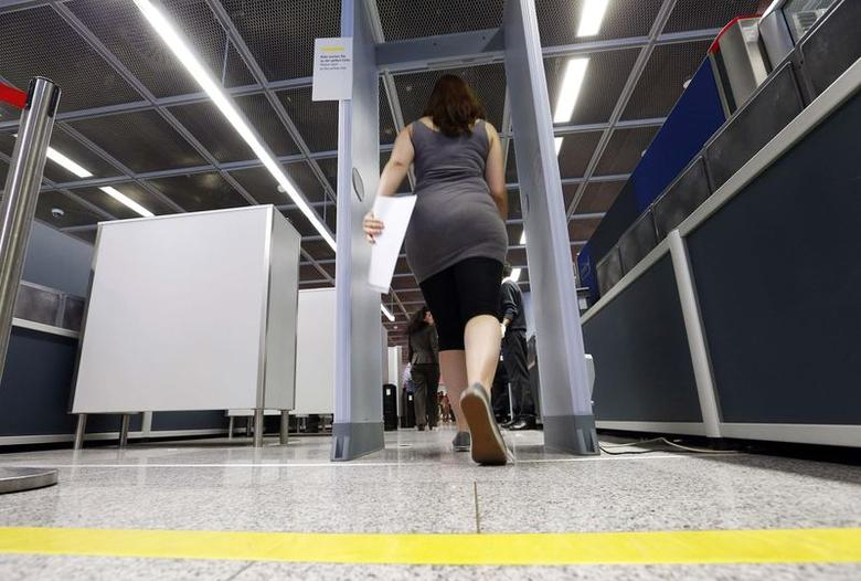 A passenger walks through a security checkpoint at Frankfurt Airport July 3, 2014.   REUTERS/Ralph Orlowski
