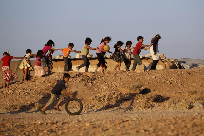 Children, who are internally displaced due to the fighting between rebels and the forces of Syrian President Bashar al-Assad, play inside Al-Tah camp in the southern Idlib countryside July 4, 2014. Picture taken July 4, 2014. REUTERS/Khalil Ashawi
