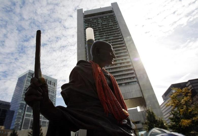A statue of Mahatma Gandhi stands in the Occupy Boston encampment, with Boston's Federal Reserve Building in the background, in Boston, Massachusetts October 11, 2011. REUTERS/Brian Snyder/Files