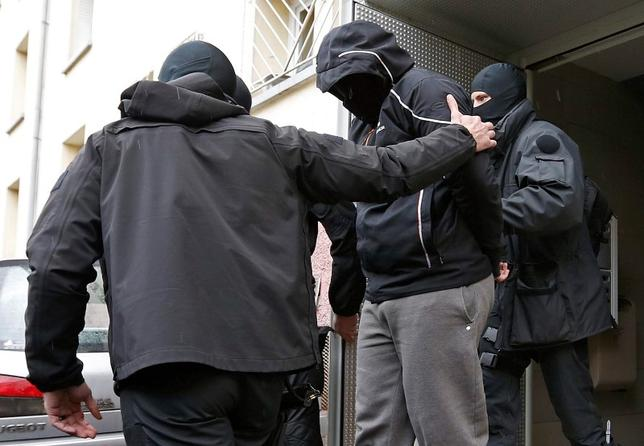 French special Police forces escort a suspect from a residential building in the Meinau suburb of Strasbourg, May 13. 2014. REUTERS/Vincent Kessler