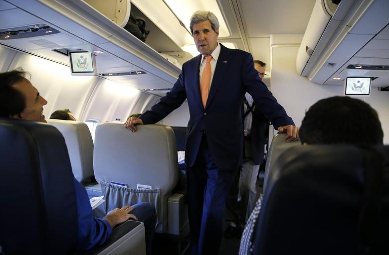 U.S. Secretary of State John Kerry greets media representatives flying aboard his plane bound for diplomatic talks in China while flying out of Washington, July 7, 2014. ''   REUTERS/Jim Bourg