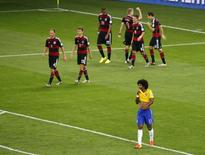 Alemães comemoram gol contra o Brasil enquanto Dante lamenta. 08/07/2014          REUTERS/Leonhard Foeger
