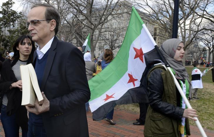 Chief Syrian Opposition Coalition negotiator Hadi al-Bahra (L) awaits his turn to address dozens of protestors gathered to mark the third anniversary of the Syrian revolution in Lafayette Park, across from the White House, in Washington, March 15, 2014.       REUTERS/Mike Theiler
