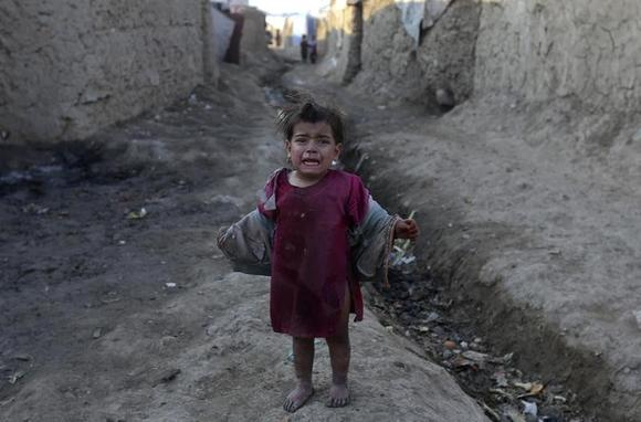 An internally displaced Afghan girl stands outside her shelter at a refugee camp in Kabul, January 14, 2014. REUTERS/Omar Sobhani