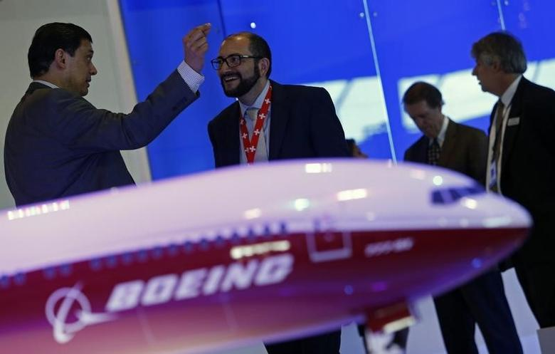 Visitors talk next to a Boeing 777X aircraft model at the Singapore Airshow February 13, 2014. REUTERS/Edgar Su/Files