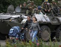 Жители Славянска на фоне украинской техники и военнослужащих 8 июля 2014 года. REUTERS/Gleb Garanich