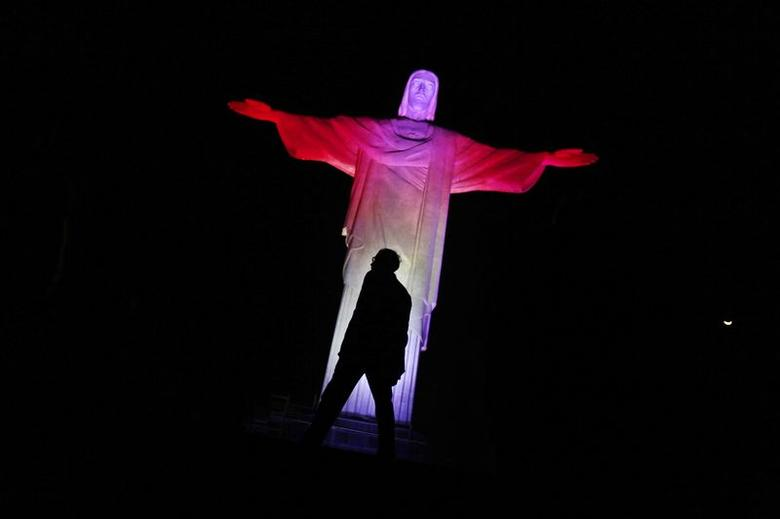 The statue of Christ the Redeemer is lit up in Canada's official colours, red and white, for Canada Day in Rio de Janeiro, July 1, 2014. REUTERS/Pilar Olivares