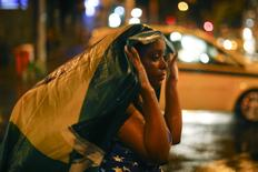 A Brazil soccer fan walks in the rain after watching a broadcast of their team's loss against Germany in their 2014 World Cup semi-final match, in Rio de Janeiro July 8, 2014.  REUTERS/Jorge Silva