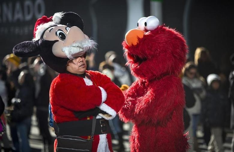 Men dressed as Santa Mickey Mouse (L) and Elmo take a break from posing with tourists for tips, and talk in Times Square in New York, December 28, 2013.      REUTERS/Carlo Allegri