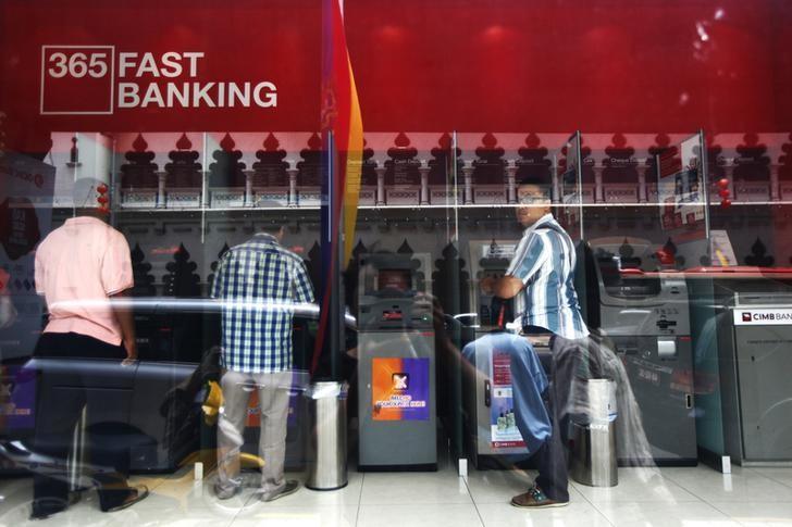 People use CIMB automated teller machines (ATMs) in Kuala Lumpur February 25, 2014. REUTERS/Samsul Said