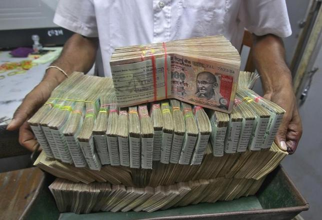 An employee poses with the bundles of Indian rupee notes inside a bank in Agartala August 22, 2013. REUTERS/Jayanta Dey