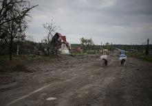 Люди едут на велосипедах по разрушенному в результате обстрелов поселку Семеновка 9 июля 2014 года. Евросоюз согласовал пополнение 11-ю фамилиями списка лиц, которым будет запрещён въезд и заморожены активы из-за противостояния на Украине, где в четверг продолжилось длящееся несколько месяцев кровопролитие. REUTERS/Gleb Garanich