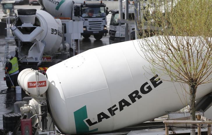Concrete mixing trucks are seen at Lafarge concrete production plant in Pantin, outside Paris, April 7, 2014.  REUTERS/Christian Hartmann
