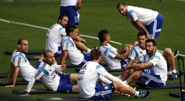 Argentina's national soccer team player Javier Mascherano (2nd L) talks to teammate Lucas Biglia (C) as they sit with Ezequiel Lavezzi (R), Martin Demichelis (2nd R) and Rodrigo Palacio (R, standing) during a training session ahead of their 2014 World Cup final match against Germany, in Vespasiano July 10, 2014.  REUTERS/Marcos Brindicci