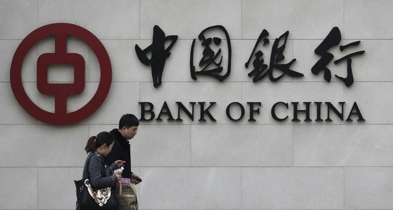 Pedestrians walk past a Bank of China sign at its branch in Beijing March 26, 2013. REUTERS/Kim Kyung-Hoon