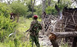 Policemen stand guard at a homestead after gunmen attacked Hindi village, near Kenya's coastal town of Lamu, July 6, 2014.  REUTERS/Joseph Okanga